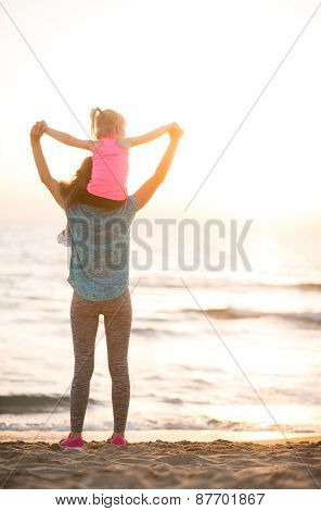 Baby Girl Sitting On Shoulders Of Mother And Rejoicing While On