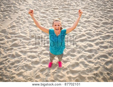 Full Length Portrait Of Fitness Young Woman Rejoicing On Beach