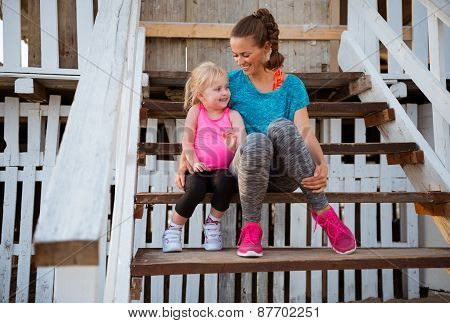 Fitness young woman with baby girl sitting on stairs of beach house