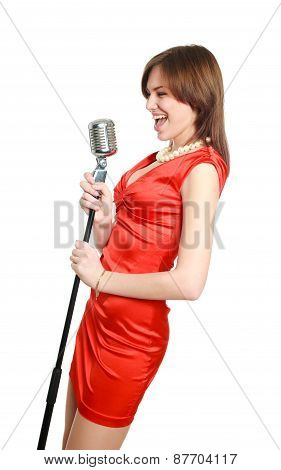 Attractive Young Girl In A Red Dress Singing Into A Microphone, Studio, Isolated On White