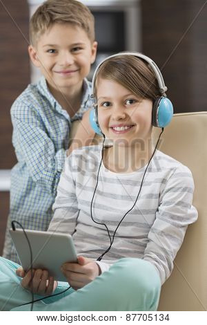 Portrait of cute girl listening music on digital tablet while brother standing behind her