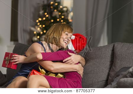 Happy mother hugging girl during Christmas at home