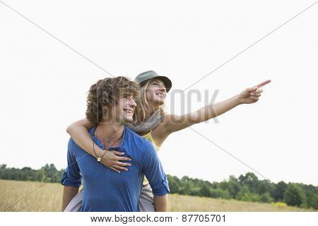 Happy woman showing something while enjoying piggyback ride on man in field