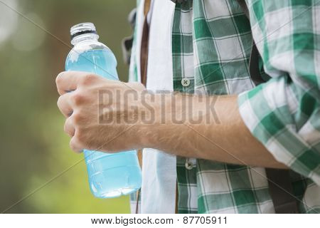 Midsection of man with energy drink outdoors