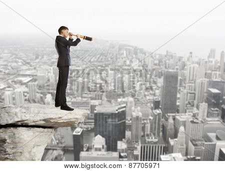 Businessman looks through a telescope. Concept for business