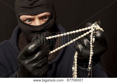 Thief. Man in black mask with a pearl necklace. Focus on pearl necklace