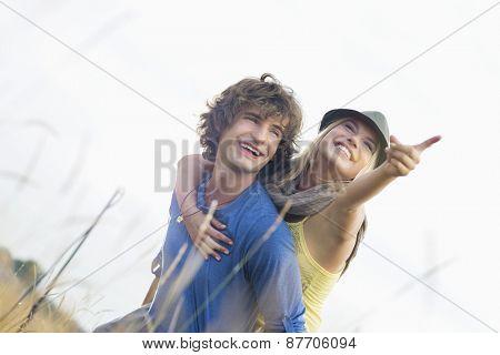 Happy woman enjoying piggyback ride on man in field