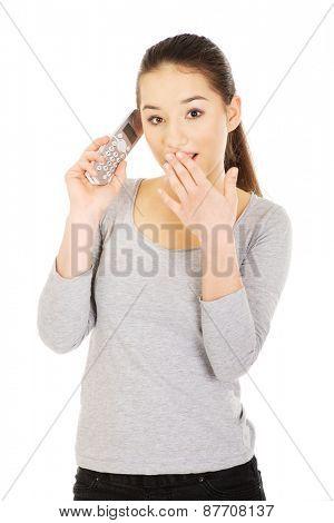 Shocked teenage woman talking on the phone.