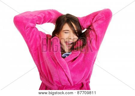 Beautiful stretching and yawning woman wearing pink bathrobe.