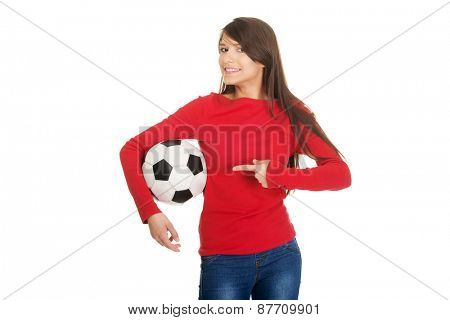 Active woman pointing on a soccer ball.