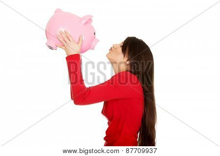 Happy student woman kissing her piggy bank.