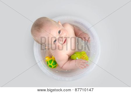 Cute Baby Having A Bath In Transparent Bucket And Playing With Toys