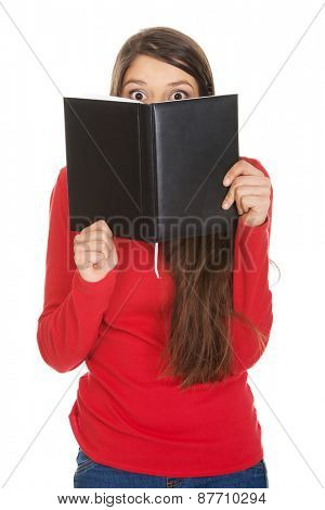 Young woman hiding her face behind a notebook.