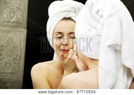 Beautiful woman squeeze her acne in front of the mirror.