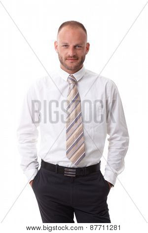 Portrait of handsome businessman standing in shirt and tie with hands in pockets, looking at camera, smiling.