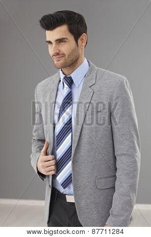Portrait of handsome businessman in grey jacket and tie, looking away.