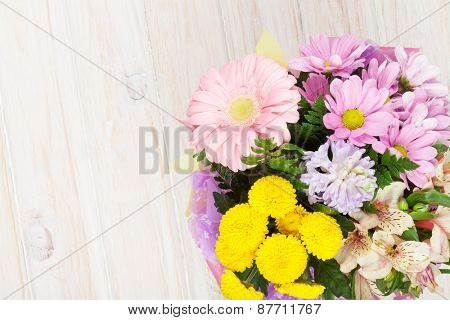 Colorful flowers bouquet on white wooden table. Top view with copy space