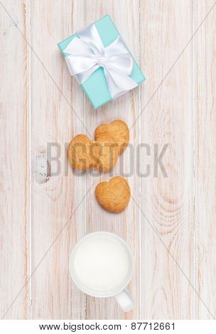 Cup of milk, heart shaped cookies and gift box on white wooden table with copy space