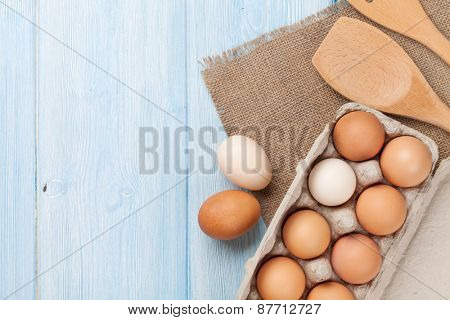 Cardboard egg box on wooden table. Top view with copy space