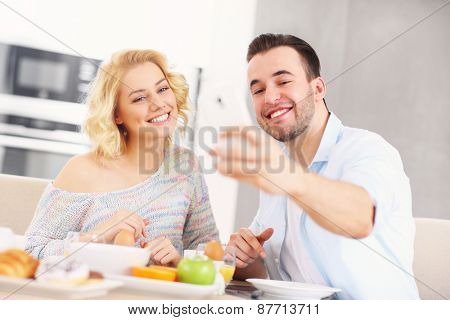A picture of a young couple eating breakfast in the kitchen and taking selfie