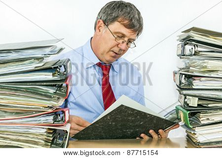 Man Studies Folder With Files At His Desk In The Office