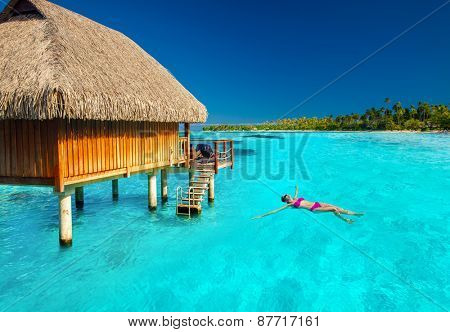 Woman swimming in tropical lagoon next to overwater villa