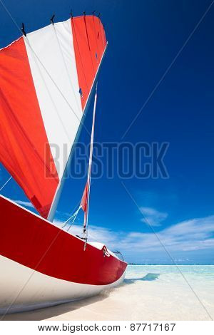 Sailing boat with red sail on a beach of deserted tropical island with shallow blue water