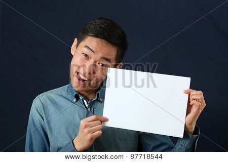Funny young Asian man showing copy space page and looking at camera