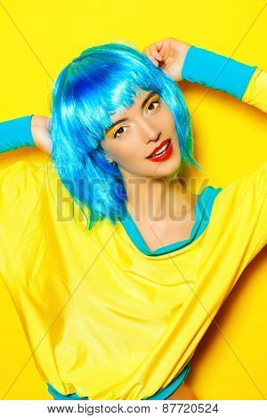 Bright glamorous girl in vivid clothes and a wig alluring over yellow background. Beauty, fashion. Cosmetics, hairtsyle.