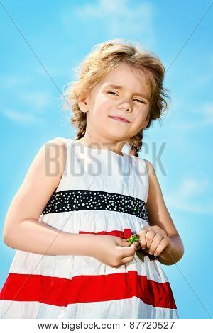 Portrait of a cute 5 year old girl on a blue sky background. Happy childhood.