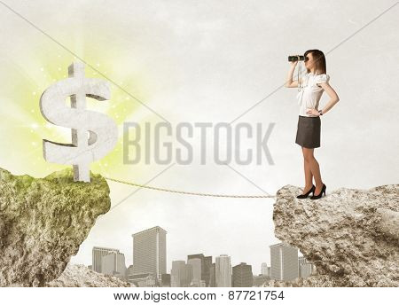 Businesswoman standing on the edge of mountain with a shining dollar mark on the other side