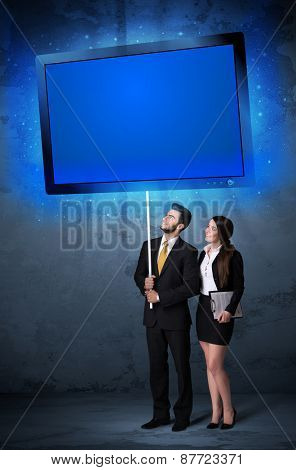 Young business couple holding a big, blue shining tablet
