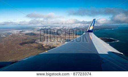 ICELAND - MARCH 23, 2015: An Icelandair jet flies low over Iceland showing the magnificent landscapes below it as it prepares to land at Keflavik International Airport in Reykjavik.