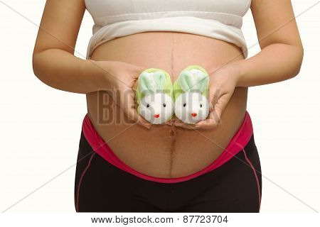 Small Shoes For The Unborn Baby In The Belly Of Pregnant Woman