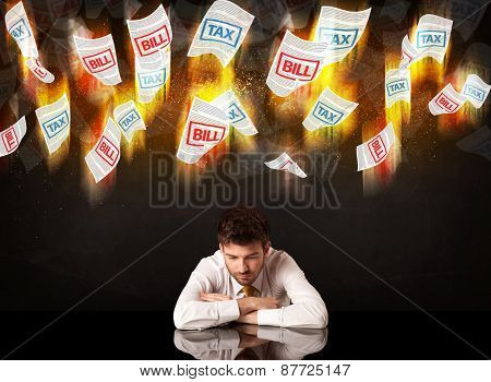 Depressed businessman sitting under falling papers