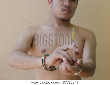 Young Man Holding  Syring In Hand With Handcuffs