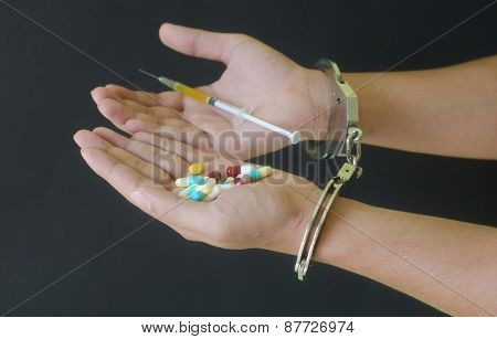 Syringe And Drug In Hand And Handcuffs