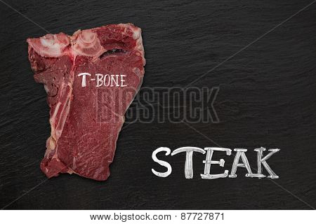 Raw beef t-bone steak onblack stone, close-up