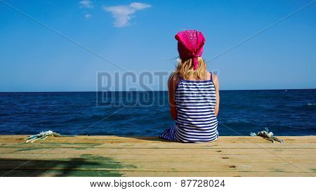 Girl In A Striped Dress Looks At The Blue Sea.