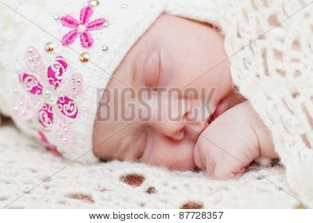 Baby Lying In Hat On Bed Under Soft White Knitted Shawl While Sleeping
