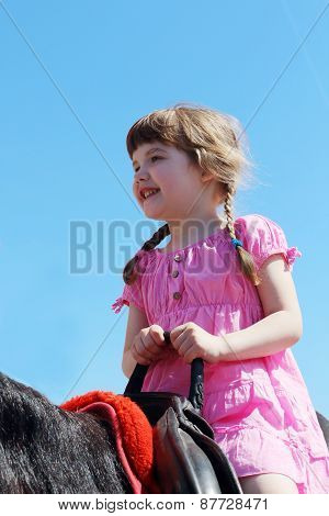 Little Beautiful Girl In Pink Dress Sits In Saddle On Brown Horse