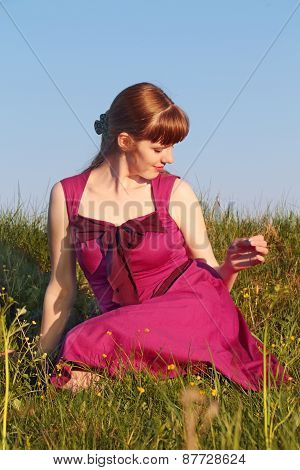 Beautiful Girl In Pink Dress Sitting On Grass Turning Her Head In Sunny Summer Day