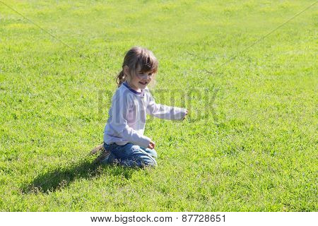 Little Cute Girl In Jeans Sitting On Grass And Laughing On Summer Day