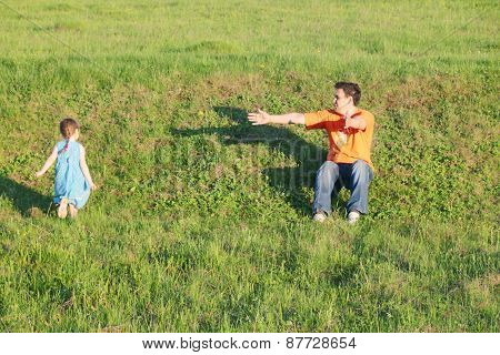 Little Cute Girl Runs Next To His Father On Grass On Summer Day