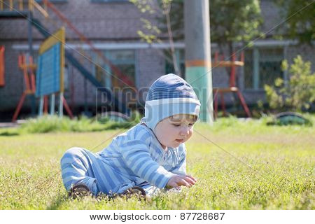 Close-up Of Cute Little Boy In Blue Striped Suit And Hat Sitting And Touching Grass