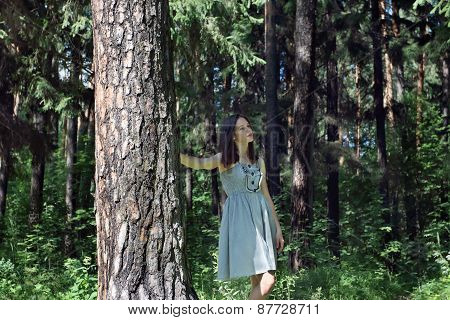 Beautiful Girl With Long Hair In Dress Walking In Woods On Summer Day, Focus On Tree
