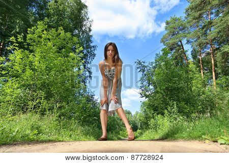 Beautiful Girl In Dress With Long Hair Standing In Middle Of Road In Woods