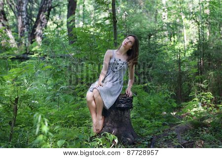 Beautiful Girl In Dress Sitting On Stump In Forest And Looking Up