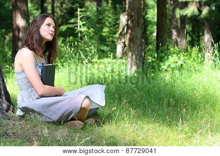 Beautiful Girl In Dress Sitting On Grass Under Tree With Book And Thinks