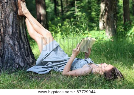 Beautiful Girl In Dress Lying Under Tree On Grass And Reading Book